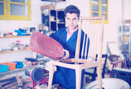 Adult craftsman wearing blue workwear repairing old chair in workshop Imagens - 110197150
