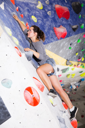 Portrait of young female mountaineer climbing artificial rock wall without belay indoors