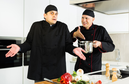 Two men cooks  in black uniform discussion and having quarrel on kitchen 写真素材