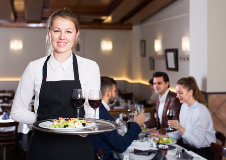 smiling young waitress with serving tray welcoming to cozy restaurant Фото со стока