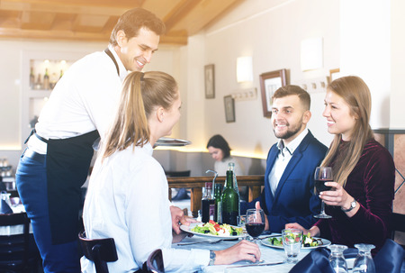 Handsome waiter serving meals to friendly company guests at restaurant