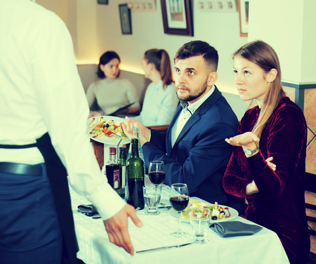 Dissatisfied young couple expressing dissatisfaction with food talking to apologetic waiter