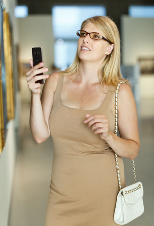 Woman with spectacles looking at exposition and taking pictures on her smartphone in museum of arts