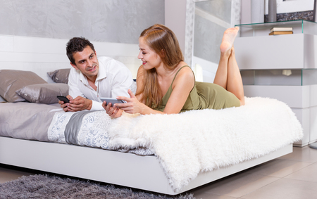 Young happy woman with her boyfriend relaxing together at home, using mobile phone 版權商用圖片