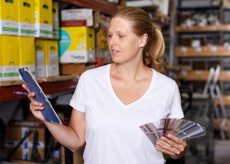 Positive young woman  standing near racks in build store holding notebook and samples
