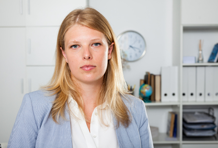 Portrait of adult confident businesswoman standing in office interior Stock Photo