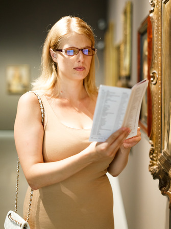 Female visitor with glasses holding information booklet in her hands looking at exhibits in art museum hall