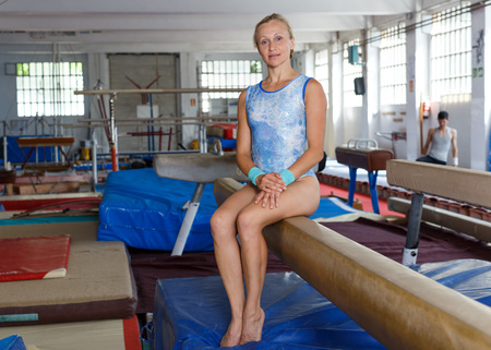 Potrait of fit woman training gymnastic elements on balance beam in acrobatic hall