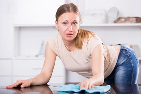 Jeune femme nettoyant dans la maison et essuyant la table Banque d'images