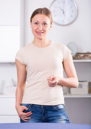 Smiling woman standing at home on clock background Stock Photo