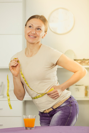 Smiling young woman measuring waist with yellow tape Banco de Imagens