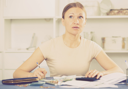 Frustrated woman facing financials troubles at table with bills, money and calculator Фото со стока