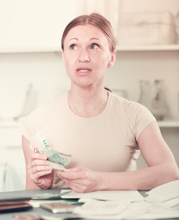 Woman sitting at table at home with calculator counting money for paying bills