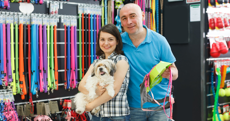Joyful family couple with dog  choosing new bowl and leash in pet store Stock fotó