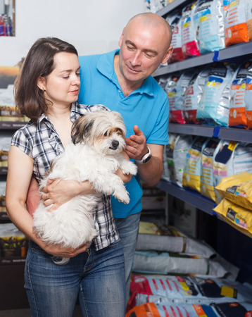 Portrait of cheerful family couple with dog buying vet food in petshop