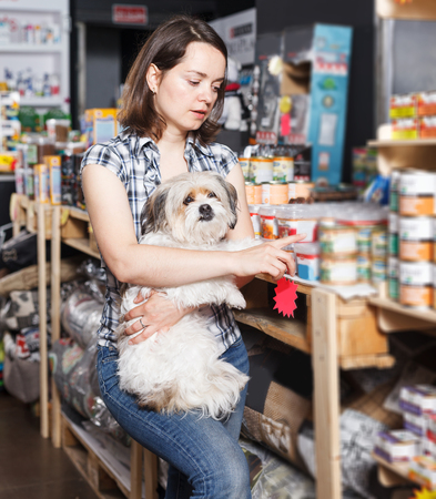 positive young female with dog selecting vet  preserves in petshop