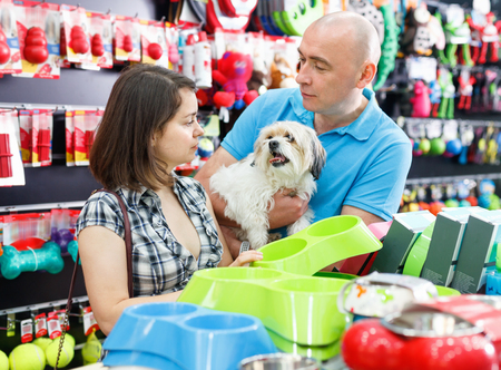 Portrait of positive glad  smiling couple purchasing new pet bowls in pet store