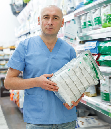 Glad man veterinarian seller with pet dry food standing near shelfs  in pet store