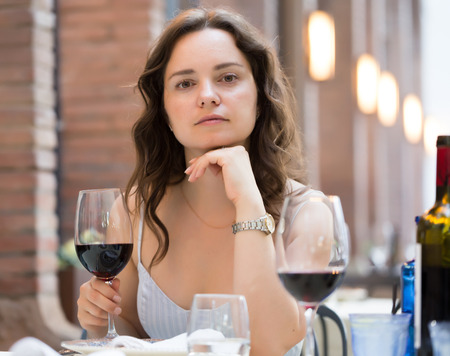Young woman with glass of red wine sitting at outdoor restaurant Stockfoto