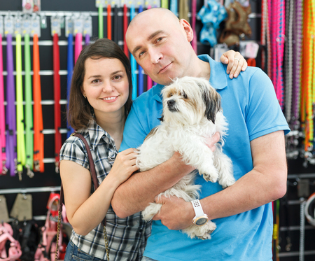 Portrait of positive couple with dog in pet shop, looking for new goods. Focus on both persons Banco de Imagens