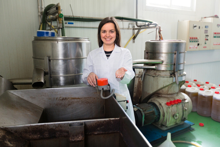 caucasian girl with flexible tubing and pot at olive oil industry