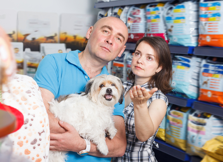 Adult family couple with dog  buying dry food for dogs in pet shop