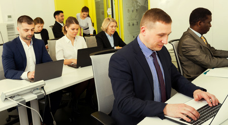 Confident businessman working on laptop in modern coworking space with multinational team