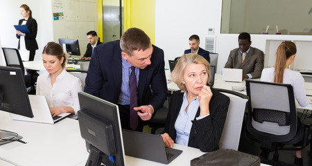 Upset mature woman sitting at laptop in coworking space while dissatisfied manager pointing out mistakes in her work