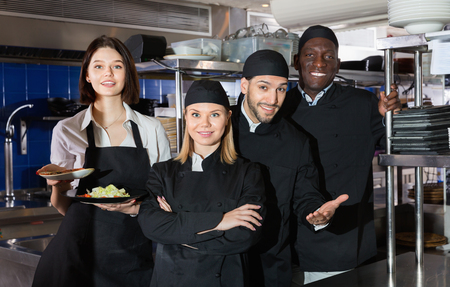 Happy cheerful smiling woman waiter with command of cooks are posing together on kitchen in restaurant. 版權商用圖片