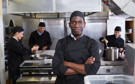 Portrait d'un chef afro-américain confiant dans la cuisine du restaurant avec un personnel professionnel occupé