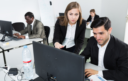 Positive young business woman explaining something to male coworker, pointing at a computer monitor at office Imagens