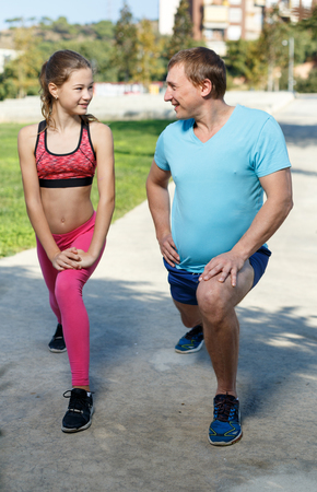Smiling sporty man and tweenager girl doing exercises together in summer park