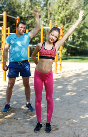 Happy tween girl stretching together with father during training outdoors in summer day