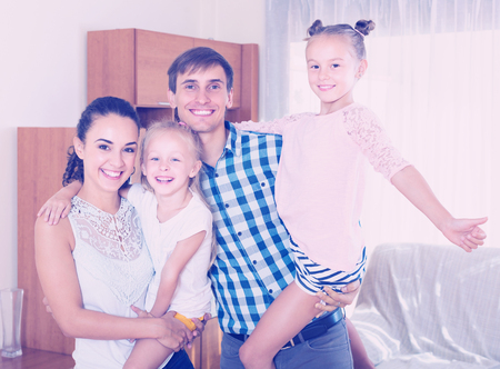 Portrait of cheerful young parents with two cute little daughters at home