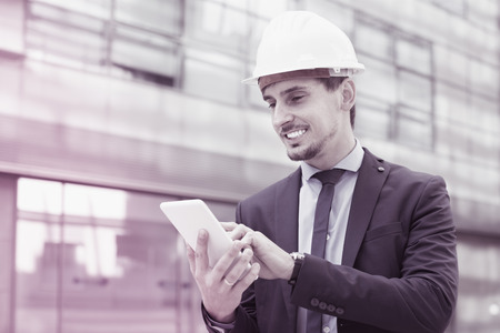 Positive male architect in helmet working at the tablet outdoors