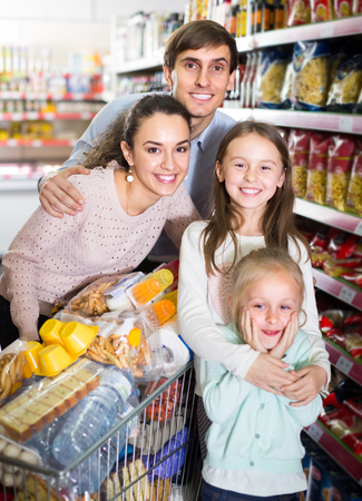 Positive parents with  kids and purchases in shopping cart Archivio Fotografico