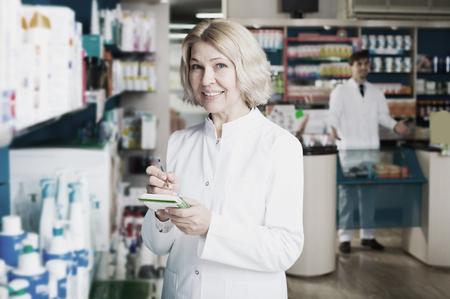 Elderly pharmacist and pharmacy technician posing in pharmacy