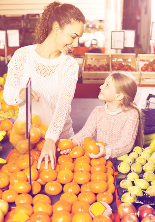 Happy positive smiling mother and little girl choosing fresh fruits in grocery 免版税图像