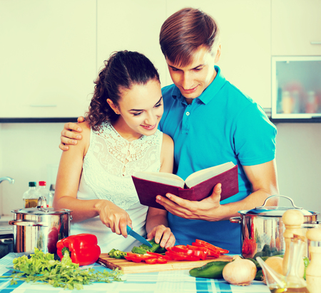 Cheerful young family couple cooking vegetables in domestic kitchen and read the book Archivio Fotografico