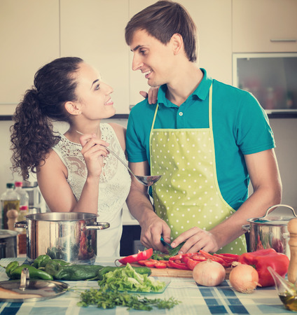 Happy man and woman standing near table with vegetables