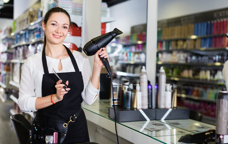 Young cheerful positive  female hairdresser holding blow dryer and hair cutters in shop