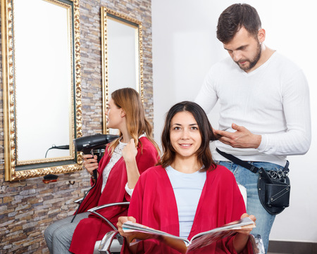 Positive glad cheerful  young man hairdresser cuts hair of young woman with magazine at salon
