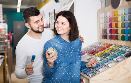 cheerful couple examining various paints in paint supplies store