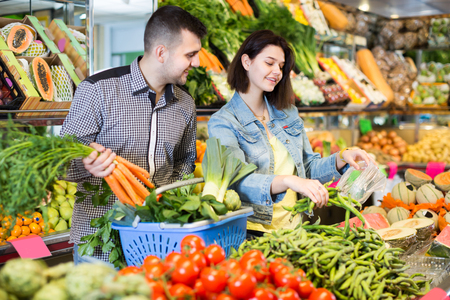 Girl and guy are deciding on vegetables in grocery shop.