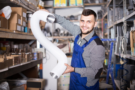 Young european  worker choosing flexible aluminum pipe for ventilation in workshop