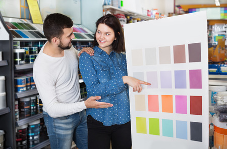 Young loving couple deciding on best color scheme at a paint supplies store. Focus on both persons