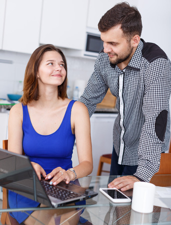 Portrait of young woman using laptop and man standing at home kitchen