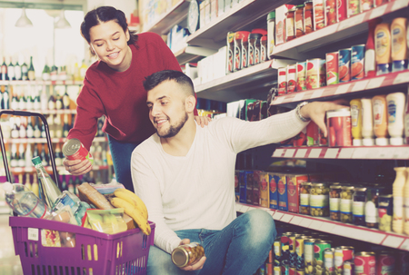 vigorous couple choosing ordinary family purchasing canned food for week at supermarket 免版税图像