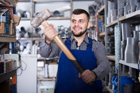 Smiling construction worker display a professional hammer in the working warehouse
