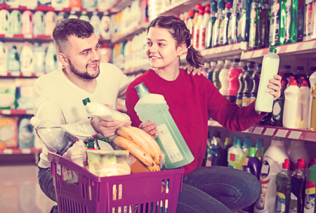 two cheerful adult people in good spirits selecting detergents оn the shelves in the store